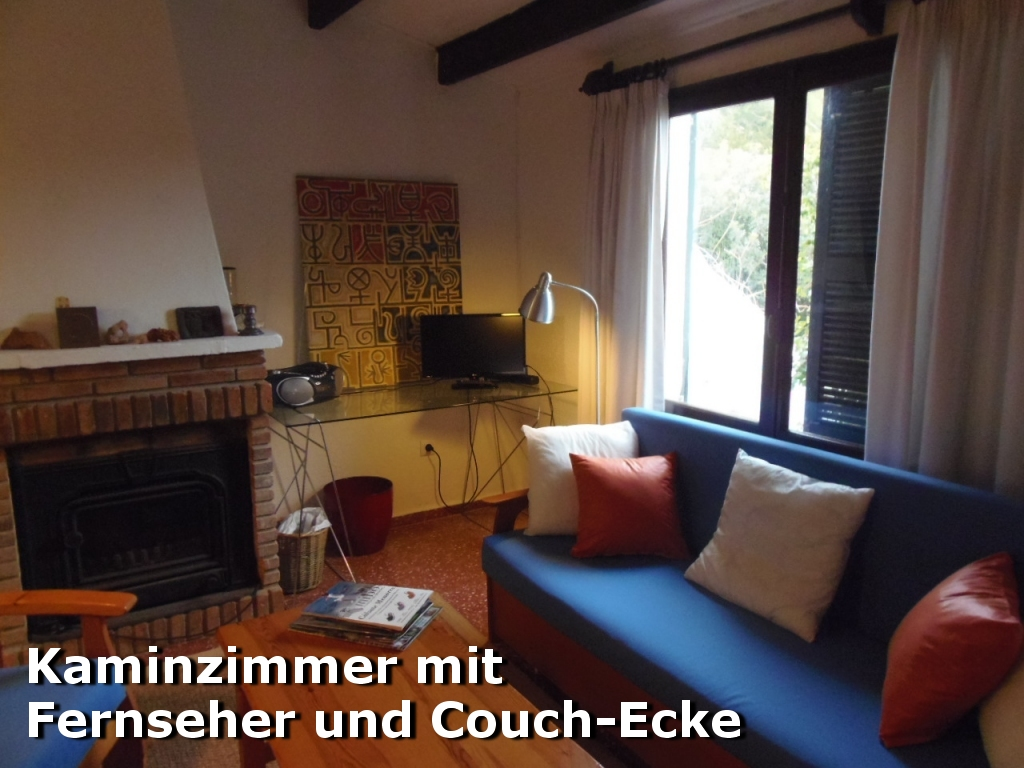 Kaminzimmer mit Couch und Fernseher in der Villa Hibiscus